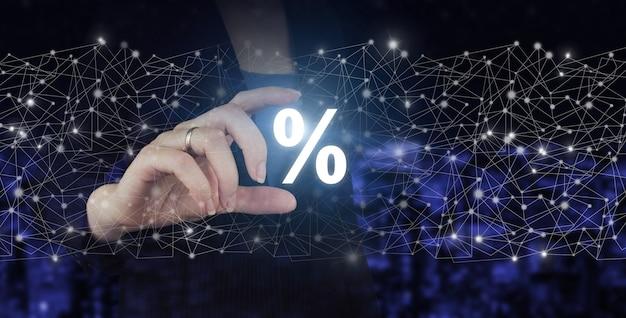 Kortingen geven aan klanten. hand houden digitale hologram procentteken op stad donkere onscherpe achtergrond. een digitaal concept van korting en commissie.
