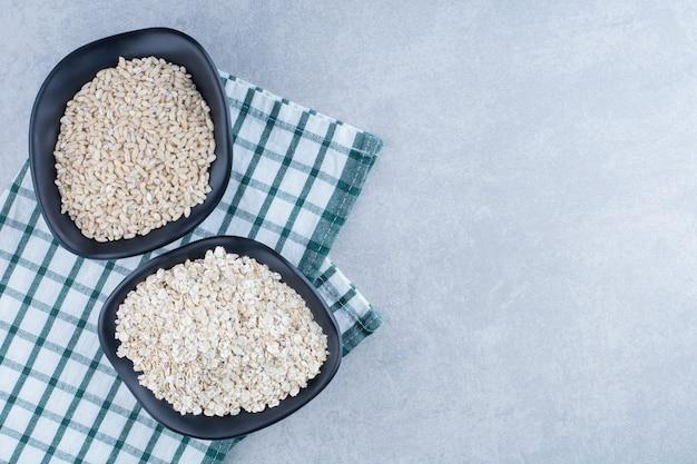 Kortkorrelige rijst en haver opgestapeld in twee zwarte kommen op gevouwen tafelkleed op marmeren achtergrond.