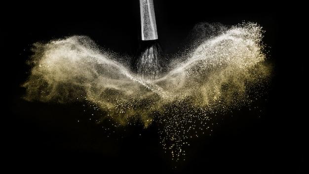 Kosmetische borstel met het gouden kosmetische poeder uitspreiden