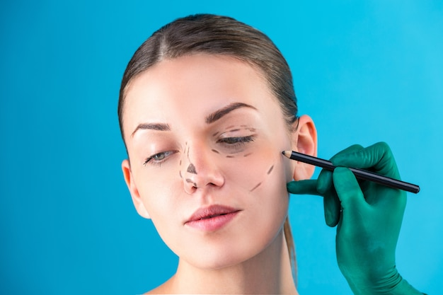 Kosmetische chirurg die vrouwelijke cliënt in bureau onderzoekt. arts trekt lijnen met een marker, het ooglid voor plastische chirurgie, ooglidcorrectie. chirurg of schoonheidsspecialist handen vrouw gezicht aan te raken. neuscorrectie