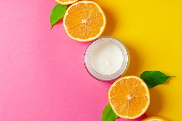 Kosmetische fles met gesneden citrusvruchten op heldere roze achtergrond