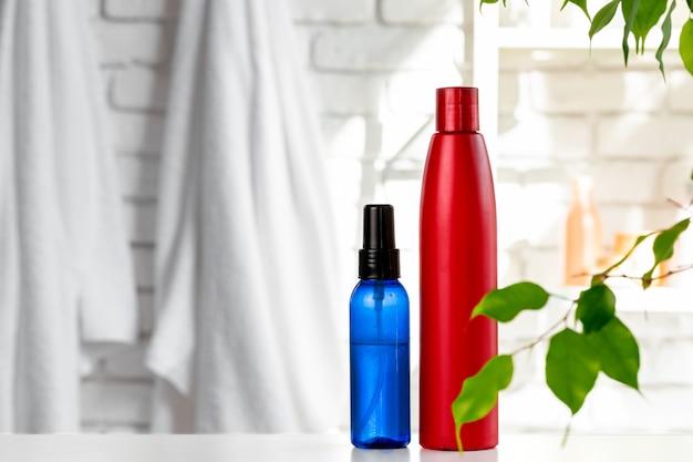 Kosmetische flessen tegen de witte achtergrond van de badkamersmuur