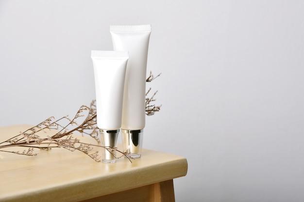 Kosmetische flessencontainers die met bladeren verpakken en copyspace