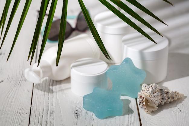 Kosmetische flessencontainers met groene kruidenbladeren, leeg etiketpakket, het natuurlijke organische concept van het schoonheidsproduct