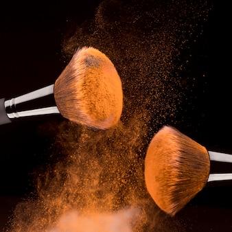 Kosmetische hulpmiddelen en oranje poeder op zwarte achtergrond