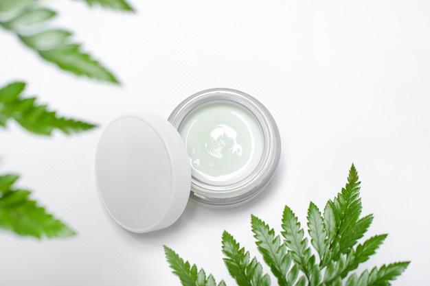 Kosmetische room in container en verse groene bladeren op wit. zelfgemaakte spa, potje biologische crème, natuurlijke cosmetica, schoonheidsproducten