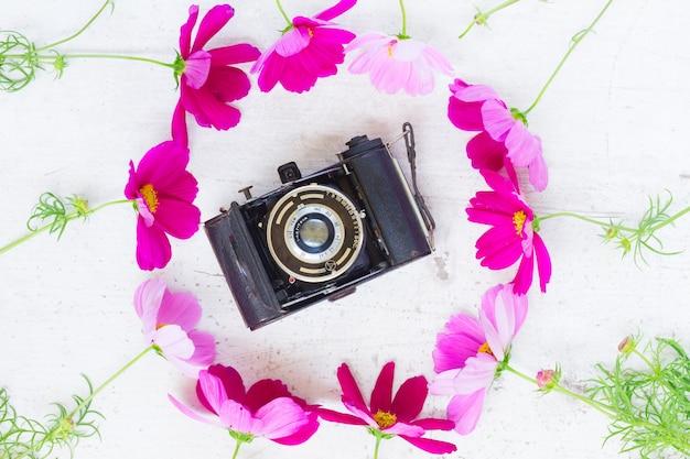 Kosmos en jasmijnbloemen met retro camera