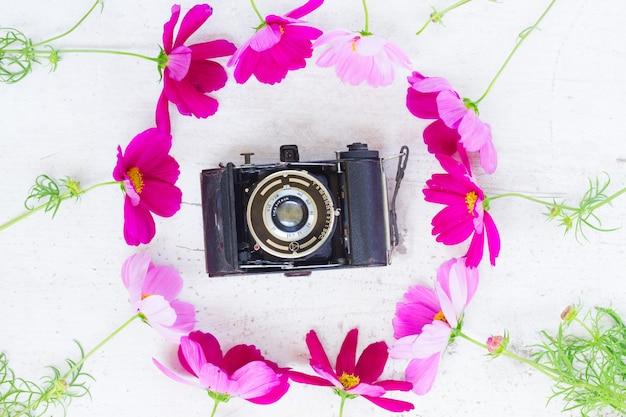 Kosmos en jasmijnbloemen met retro fotocamera