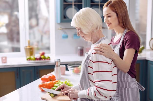 Kostbare band. charmante jonge vrouw die zich hecht aan haar bejaarde moeder tijdens het koken met haar samen, de oudere vrouw die groenten snijdt