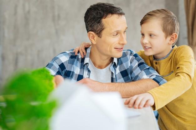 Kostbare band. charmante pre-tienerjongen die zijn vader knuffelt en met hem praat terwijl hij zich aan hem hecht tijdens het bezoek aan de werkplek van zijn vader