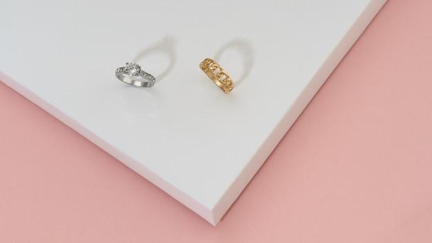 Kostbare gouden ringen met diamanten op witte en roze achtergrond