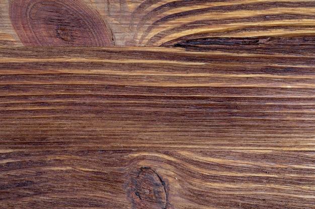 Kostbare houtstructuur. van een rustiek aspect en donkere, oker, bruine, geroosterde, zwarte tinten. de aderen en knopen worden gewaardeerd.