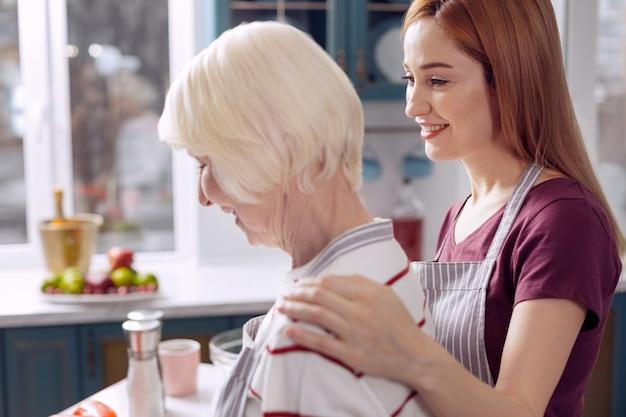 Kostbare samenwerking. schattige jonge vrouw haar moeder knuffelen terwijl ze schorten dragen en samen koken in de keuken