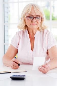 Kosten berekenen. geconcentreerde oudere vrouw die een rekening vasthoudt en iets in haar notitieblok schrijft terwijl ze aan tafel zit