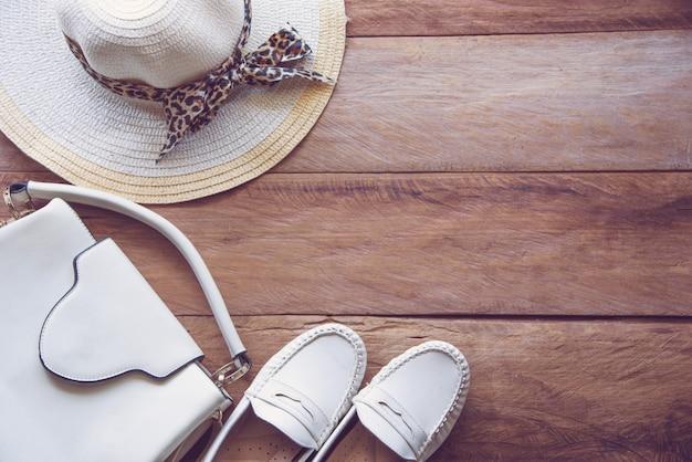 Kostuum witte toon voor vrouwen, tassen, schoenen en hoed op houten vloer - een levensstijlconcept.