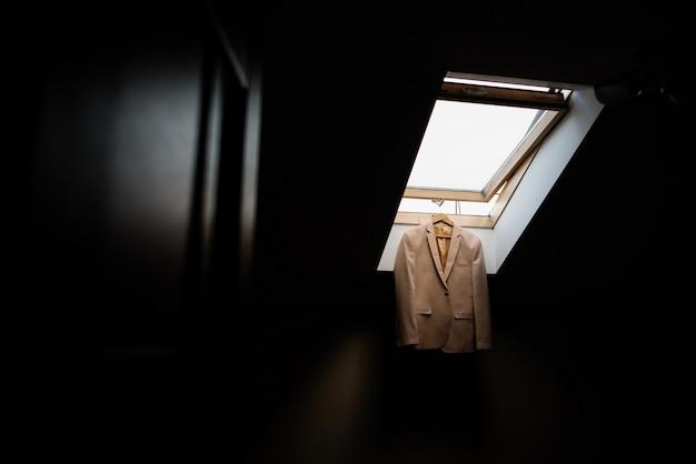 Kostuumjas hangt aan een raam aan een plafond