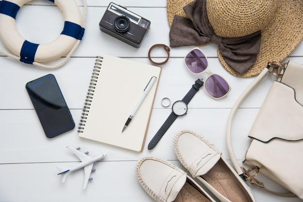 Kostuums voor reisaccessoires voor dames. paspoorten, de kosten van reiskaarten die zijn voorbereid voor de reis op een witte houten vloer