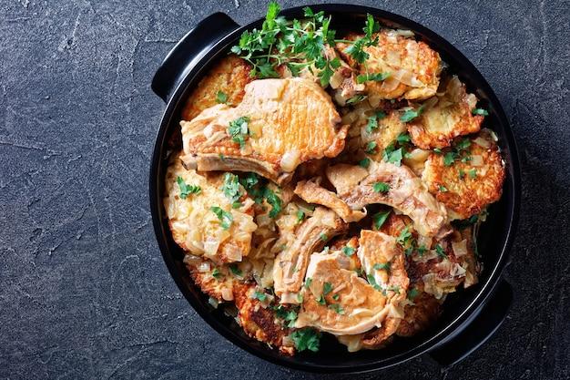 Koteletten en hash brown stoofpot met ui, horizontale weergave van bovenaf, flatlay, kopieerruimte