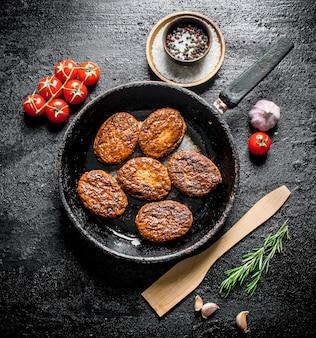 Koteletten in de pan met een houten spatel en kers op zwarte rustieke tafel