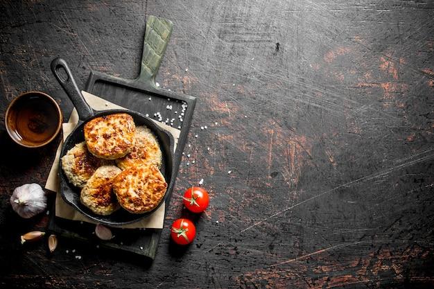 Koteletten in de pan op papier met knoflook en tomaten op donkere rustieke tafel