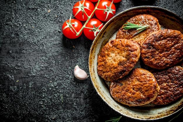 Koteletten in pan met tomaten, rozemarijn en knoflook. op zwarte rustieke achtergrond