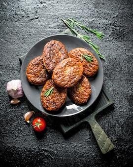 Koteletten met knoflook en rozemarijn op zwarte houten tafel