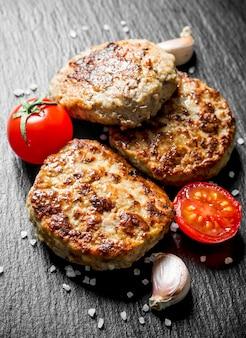 Koteletten met knoflookteentjes en tomaten. op zwarte rustieke achtergrond