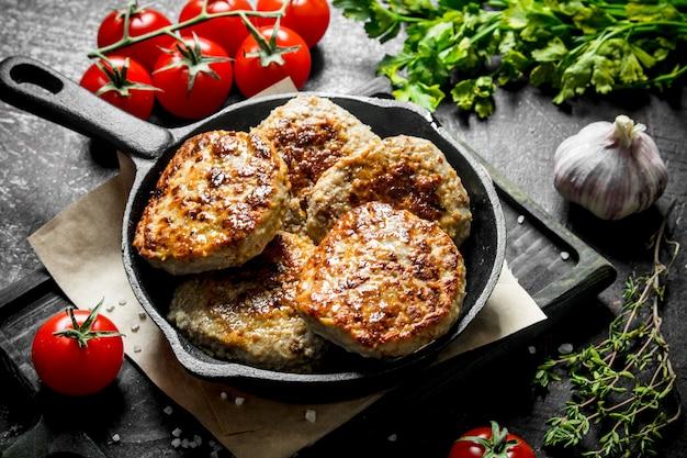 Koteletten met peterselie, tomaten en knoflook op houten tafel