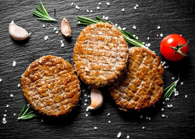 Koteletten met stukjes zout, rozemarijn en knoflook op donkere rustieke tafel