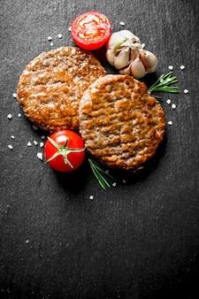 Koteletten met tomaten, knoflook en rozemarijn op zwarte houten tafel