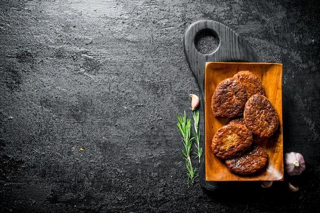 Koteletten op een bord met rozemarijn en knoflook. op zwarte rustieke achtergrond