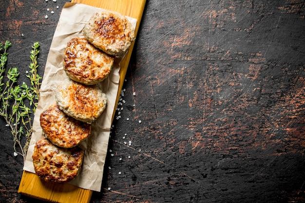 Koteletten op papier met tijm op donkere rustieke tafel