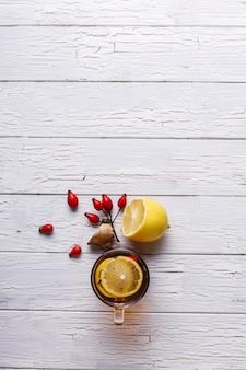 Koud behandelen. hete thee met citroen en bessen staat op witte houten tafel