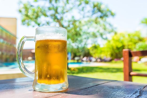 Koud bierglas op tafel in het openluchtcafé.