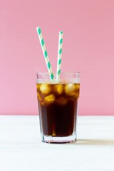 Koud brouwsel. koffie met ijs en gestreepte rietjes in een glas