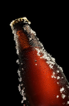 Koud bruin flesje bier met waterdruppeltjes en ijs