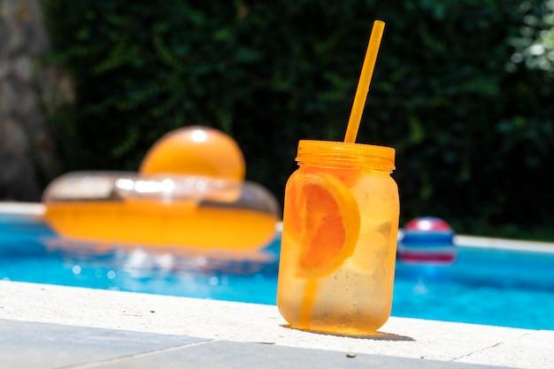 Koud drankje in de zomer. oranje metselaarkruik op bord van een zwembad