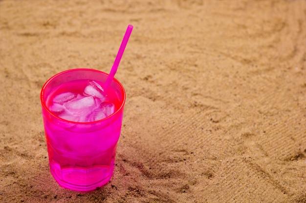 Koud drankje met ijs op een zandstrand