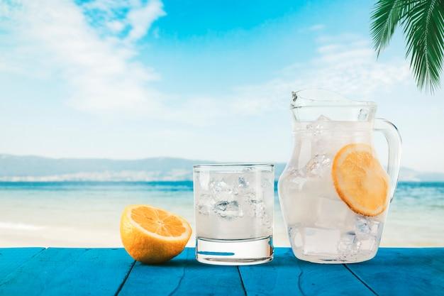 Koud en vers gemaakte limonade met ijs op een tropisch strand