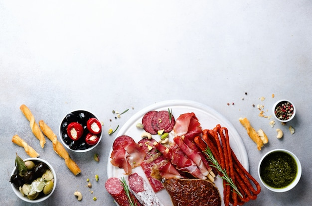Koud gerookte vleesplaat. traditionele italiaanse antipasto, snijplank met salami, prosciutto, ham, varkenskarbonades, olijven op grijs. bovenaanzicht, kopie ruimte, plat leggen