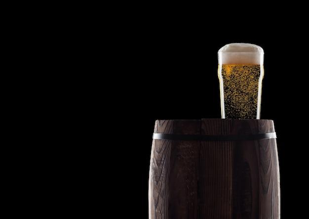 Koud glas ambachtelijk bier op oude houten vat op zwart met dauw en bubbels.