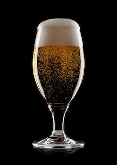 Koud glas lagerbier ambachtbier met schuim en bellen op zwarte achtergrond