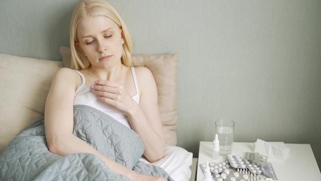 Koud griepseizoen, loopneus. ziek meisje op bed niezen in zakdoek in slaapkamer.