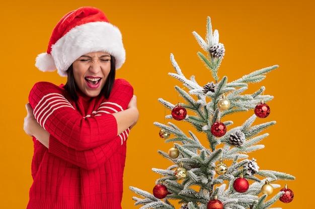 Koud jong meisje met kerstmuts staande in de buurt van versierde kerstboom omhelzen zichzelf met strak gesloten ogen geïsoleerd op oranje muur