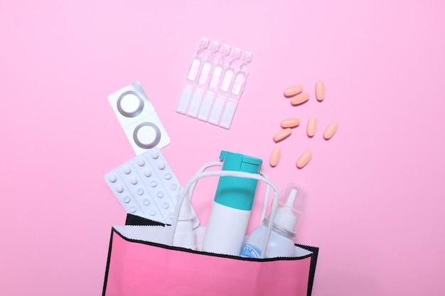 Koud seizoen, een pak medicijnen op een roze achtergrond.
