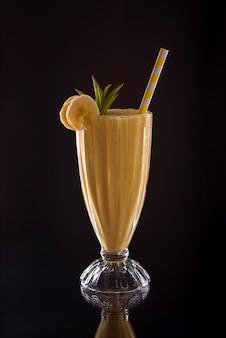 Koud verfrissend banaanijs vers met cocktailbuis op zwarte achtergrond