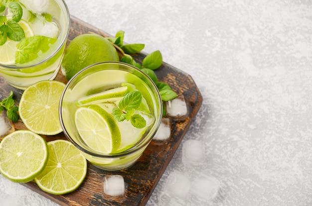 Koud verfrissende zomerdrank met limoen en munt in een glas op een grijze betonnen of stenen tafel.