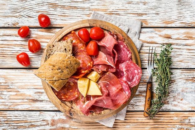 Koud vlees bord, charcuterie traditionele spaanse tapas op een houten bord. witte houten achtergrond. bovenaanzicht.