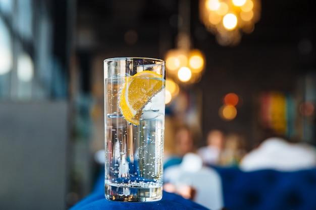Koud water in een transparante sakan met ijs met citroen.