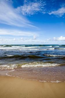 Koud winderig weer in augustus, zeekust met veel golven door winderig weer, oostzee in de zomer